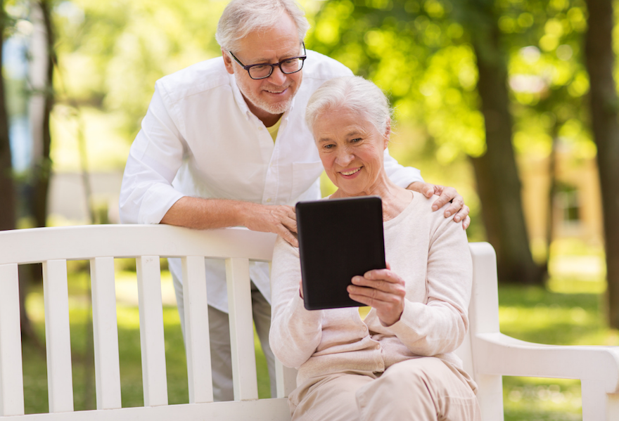 Smiling seniors sit outside and look at a tablet.